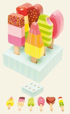 """TV284: Ice-lollies   New addition to the honeybake collection:  6 brightly painted solid rubber wood """"ice-lollies""""  complete with a wood holder & presented in a colour window box  3 years+    Height: 110mm"""