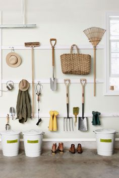 Utilize Shaker-style peg rails to hang outdoor essentials. In addition to single pegs, you can double up to create spots for hanging tools, like the broom and rake above, by their heads. With three closely spaced pegs, even boots have a home.   - CountryLiving.com