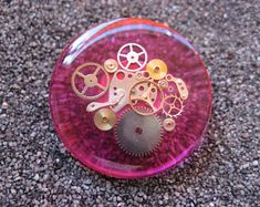 """Large Steampunk """"Gears of time"""" ring on a pink background in resin mounted on an easily adjustable support - diameter 35 mm"""