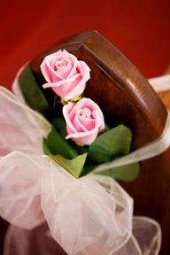 two simple roses tied to the pew with tulle or organza - church wedding decorations