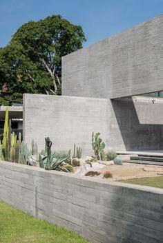 Stu/D/O Architects a conçu une résidence en béton avec des espaces de vie aux parois vitrées donnant sur les jardins et une piscine. Fonctionnant comme un abri intime, Casa de Alisa se caractérise par des ouvertures stratégiquement placées, apportant de la lumière naturelle tout en assurant suffisamment d'intimité à ses occupants. Défini par l'intersection de plans de béton ressemblant à l'architecture brutaliste, le bâtiment minimaliste de deux étages semble monolithique, tout en offrant… Exposed Concrete, Concrete Wood, Spa Rooms, Glass Balustrade, Glass Centerpieces, Construction Cost, Luxury Dining Room, Staircase Design, Open Plan Living