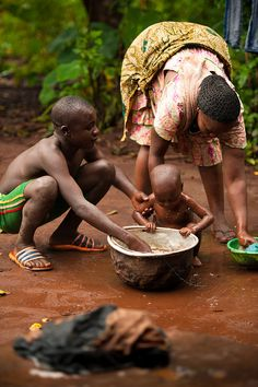 Africa |  An other brother and a mother bath a younger brother/son | ©  Silatjunkie, via Flickr