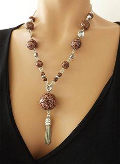 *Voir aussi bracelet assorti dans la même collection* Perles et motif réalisés à la main en pâte polymère. Les perles sont cuites, poncées puis vernis. Montées sur une chaîne et fermoir en métal argent, ce bijou est agrémenté de perles en métal. Longueur: 54cm. Modèle unique.