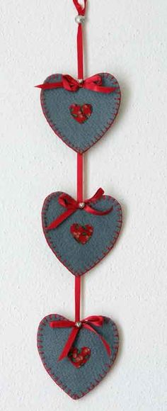 Handmade Seasonal Gift gift idea by Janys Hyde found on MyOwnCreation: Handmade wall hanging, grey felt hearts with Tyrolean printed cotton hearts in the centre of each. Blanket-stitched around the edges and attached to a deep red satin ribbon with loop for hanging at the top end. Each felt heart is completed with a small satin ribbon and tiny pewter heart.