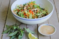 Thai Chicken Salad from Comfy Belly.  Ingredients: chicken, garlic, chilies or pepper flakes, fish sauce, soy sauce [sub. coconut aminos for paleo], vinegar, maple syrup or honey [only 2 T!], lime juice, toasted sesame oil, almond butter, water. #paleomaindish #paleoside