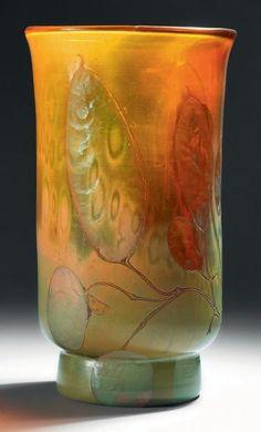 Émile GALLÉ (1846-1904)  Vase cylindrique sur talon et col évasé légèrement polylobé à chaud. Épreuve réalisée en verre ambré nuancé rouge. Décor de monnaies du pape ciselé et entièrement repris à la meule sur fond d'oxydes irisés et flammés. Signé. Hauteur: 16,5 cm - Diamètre du col: 9,5 cm Provenance: collection personnelle d'Émile Gallé, resté dans sa descendance