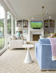 sunroom with floor to ceiling windows | blue sofa with lavender throw | design by jenkins interiors | blueprinstore.com