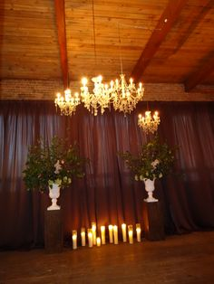 Ceremony backdrop w/ chandeliers, candles, and large floral. #studioag #studioagdesign