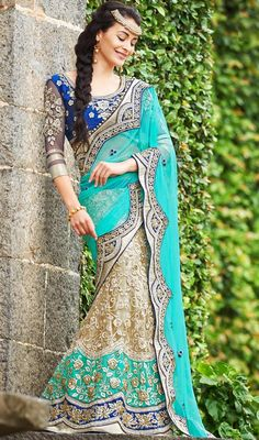 Make a stand-out statement with this cyan blue color net raw silk embroidered lehenga sari. The fantastic saree creates a dramatic canvas with wonderful lace and resham work. Upon request we can make round front/back neck and short 6 inches sleeves regular saree blouse also. #ExclusiveTurquiseAndBluePartyWearLehengaSari