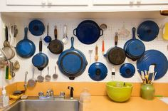 Judith Jones' collection of blue enamel cast iron, some of it passed down from Julia Child, stored on a Julia-style peg-board