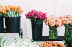 spring florals like peach ranunculus, vivid pink roses, orange tulips and bright green fern