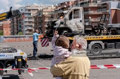 A man and a young child watch as workers remove the remains of a campervan which caught fire killing three sisters in a shopping centre car park on May 10, 2017 in Rome, Italy. The 3 victims aged 20, 8 were killed in the campervan which housed a Roma family made up of 2 parents and their 11 children. Rome investigators have opened a homicide investigation after traces of flammable liquid were found outside the vehicle.