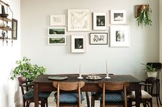 dining room design. midcentury dining room table with wall collage of picture frames and house plants