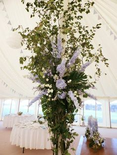 Close up of one of the floor to ceiling trees in the marquee made of flowers and foliage, with fairy lights intertwined.