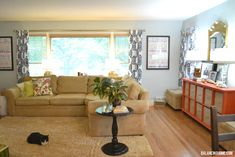 Family friendly living room-- love the bright colored sideboard for toy storage