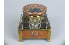 AN ARTS & CRAFTS STYLE SQUARE GLASS INKWELL, hinged circular copper cover with cast foliate motif
