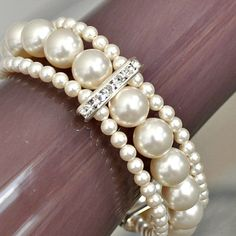 "Adorn your wrist with 3 stunning strands of crystal pearls, with rhinestone accents. Secured with a sleek sterling silver sliding tube clasp. The width of this bracelet is 0.75"". $72"