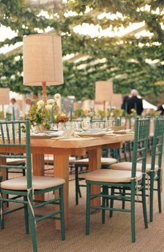 A simple wood plank table gives a natural look for this outdoor event, with wood table lamps and green Chiavari chairs picking up the warm t...