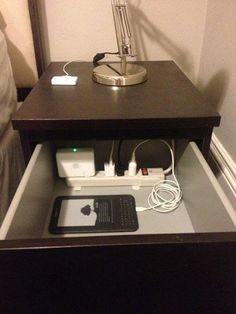 Drill a hole in the back of your night stand and place a surge protector in the drawer to keep all of your electronics neatly tucked away.