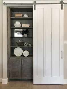 Bookshelf with cabinets below in EVRGRN Rok gray hidden by barn door