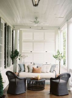 White porch with louvered shutter screen and dark brown wicker