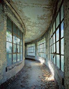 """Eerie Ellis Island, Then And Now Isolation Ward, Curved Corridor, Island """"When I photographed it on an autumn day, light dappled through the windows and gave the impression I was viewing something underwater. Ellis Island, Old Buildings, Abandoned Buildings, Abandoned Places, Abandoned Property, Through The Window, Haunted Places, Urban Decay, Beautiful Places"""