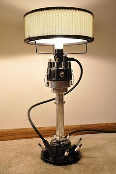 These lamps are built one at a time by a true car guy. They are built using real… These lamps are built one at a time by a true car guy. They are built using real car parts. It features a billet car distributor. The base is made from a car Car Part Furniture, Automotive Furniture, Automotive Decor, Furniture Design, Automotive Carpet, Automotive Shops, Automotive Engineering, Engineering Technology, Bench Furniture