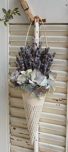 Set of Two Vintage French Book Cone with Dried French Lavender and Hydrangea The faded pages of a vintage French book provide the base for this dried arrangement. Freshly dried French Provencal lavender is accented with dried hydrangea. This fragrant bouquet would be a lovely accent for almost any room in your home! Measures approx 8 from the bottom of the cone to the top of the flowers. The width at the top of the cone including the flowers is approx. 3. The twine hanger adds 3…