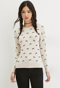 A lightweight knit sweater featuring an allover ribbon print, ribbed trim, and long sleeves.