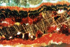 Reflected light petrographic image showing native copper sheet enclosed beneath layers of red cuprite.