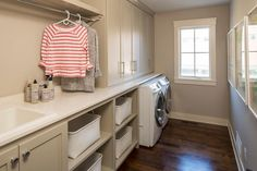 Taupe laundry room features taupe shaker cabinets and shelves lined with white wicker hamper baskets positioned under a tension rod drying rack situate dnext to an enclosed washer and dryer. Pink Laundry Rooms, Rustic Laundry Rooms, Mudroom Laundry Room, Laundry Room Remodel, Laundry Room Design, Laundry Area, Laundry Room Shelves, Laundry Room Inspiration, Room Accessories