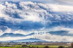Stock Photo: Early afternoon scenery of cereals fields and little town with castle between the fog, Nogales, Spain.