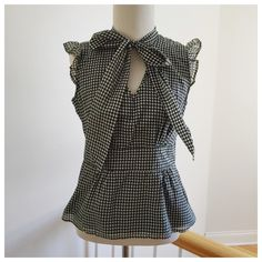 """HP 2/21 Houndstooth Banana Republic Blouse 2/21 HP, Date Night Beautiful black and white houndstooth Banana Republic blouse. There are so many great details on this top, including the ruffled sleeves and adorable front tie. Size small. 18"""" bust, 14"""" waist, 23"""" long. NWT. No PP, trades, or holds. Price is firm, unless bundled. Thanks for looking! Banana Republic Tops Blouses"""