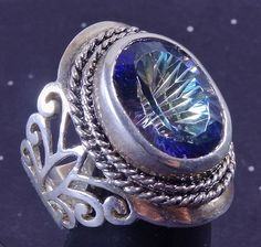 SoVintageous is offering this gorgeous sterling silver ring with a stunning bezel-set faceted Mystic Topaz.  This large ring has a thick sterling silver band with a beautiful butterfly motif on either
