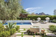 A careful layering of native trees, plantings and pots adds a sense of visual interest and privacy to the backyard area, which includes a custom-designed swimming pool and water wall, as well as a seating area focused on a fireplace.