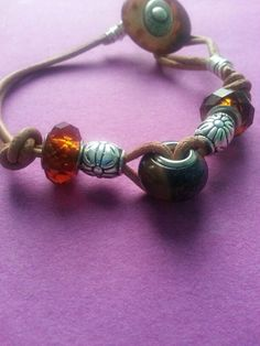 Leather bracelet with large hole beads and antique button clasp. $32