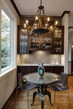 This informal dining area features wide-plank hardwood flooring, an attractive chandelier, glass-front cabinets displaying crystal stemware, and a round glass-top table with modern acrylic chairs.