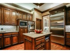 Elegant kitchen // Medium wood cabinetry // Light granite // Stainless appliances