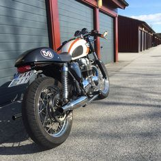 Customized white T100 Bonneville with thrust on seat and gold mirrors.