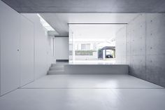a ground level void within a monolithic and windowless concrete boundary creates this dwelling's open air entry and garden.