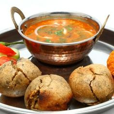 Dal Bafla Recipe - Similar to Dal Bati, these ghee laden dough balls are immensely popular in Madhya Pradesh. They are first boiled and then baked before being crumbled and topped with dal.