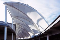 The structure consists of a series of tubular steel arches supporting a tensioned PTFE-coated glass-fibre fabric canopy covering the open-air street area between the Drama Hall and the adjacent buildings. Curved in plan, the canopy has an overall length of approximately 90m and a width of approximately 9m, and is formed by a series of …
