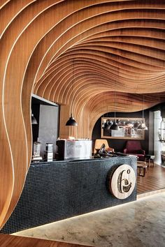 Undulating layers of timber create a cave-like interior inside this cafe in Indonesia by regional studio OOZN Style. OOZN Design installed the wavy timber Parametrisches Design, Cafe Design, Store Design, House Design, Wood Design, Design Ideas, Commercial Interior Design, Commercial Interiors, Conception Paramétrique