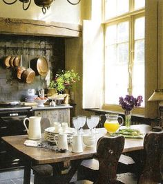 rustic Tuscan kitchen...love the copper pots and pans with the black stove and old wood table...so cozy and country!