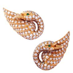Each designed as a swan curved around the lope of the ear, set with circular-cut diamonds, the eyes set with circular-cut emeralds, circa 1970, signed Van Cleef & Arpels, numbered 29540, French assay and maker's marks.