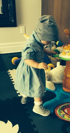 fe3773fae Baby girl wearing an empire waist denim dress with the collar up, with  studded silver