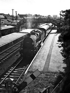 An ancient Maunsell N class loco is just weeks from scrapping as it waits at New Milton with a Bournemouth to Eastleigh local train. On the approach to electrification of the Weymouth line many steam locomotives were in a poor condition and some depots had to resort to ageing (yet steam tight) machines to maintain the services.  Hampshire, UK. Negative scan.