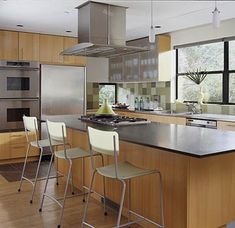 Golden beech cabinets and an island topped with honed granite span several decades of design. A sleek stainless-steel hood matches the nearby ovens, refrigerator, and dishwasher./