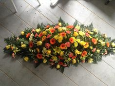 orange and yellow funeral spray, orange and yellow casket spray funeral flowers. www.thefloralartstudio.co.uk