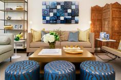 A trio of ottomans and block artwork add subtle blue color to this neutral living room. The homeowners' Indian heritage is brought into the space with an elaborate privacy screen and other accessories.